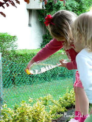 Children watering the garden with DIY homemade watering can