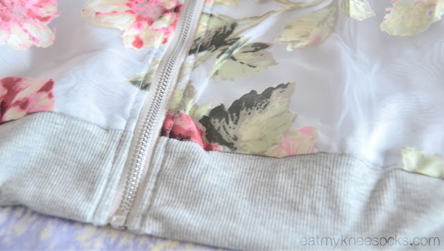 The gray hem trim on the zippered sheer floral bomber jacket from Dresslink.