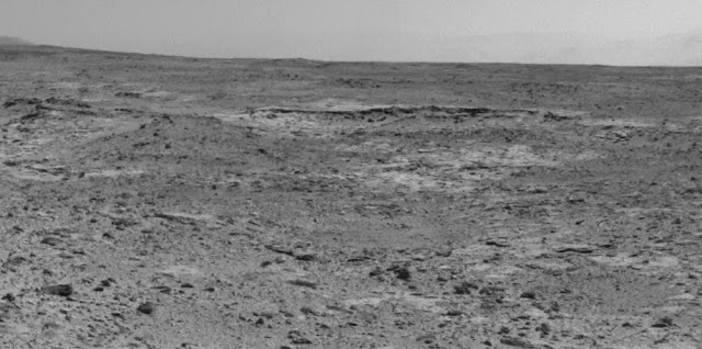 "The low ridge that appears as a dark band below the horizon in the center of this scene is a Martian outcrop called ""Cooperstown,"" a possible site for contact inspection with tools on the robotic arm of NASA's Mars rover Curiosity. Image Credit: NASA/JPL-Caltech"