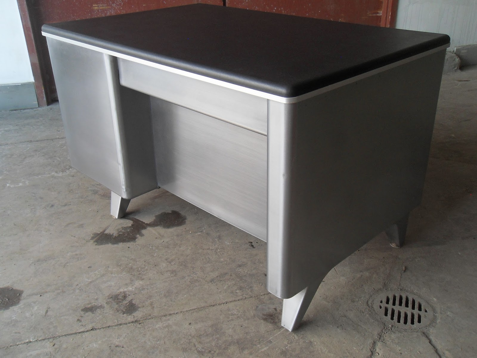 Nice little tanker desk from (I think) Cole Steel. Standard finish inside  and out. Fabricated black vinyl top.