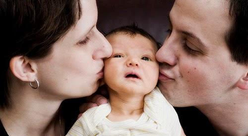 1415604381-mom-dad-kissing-baby-flickr