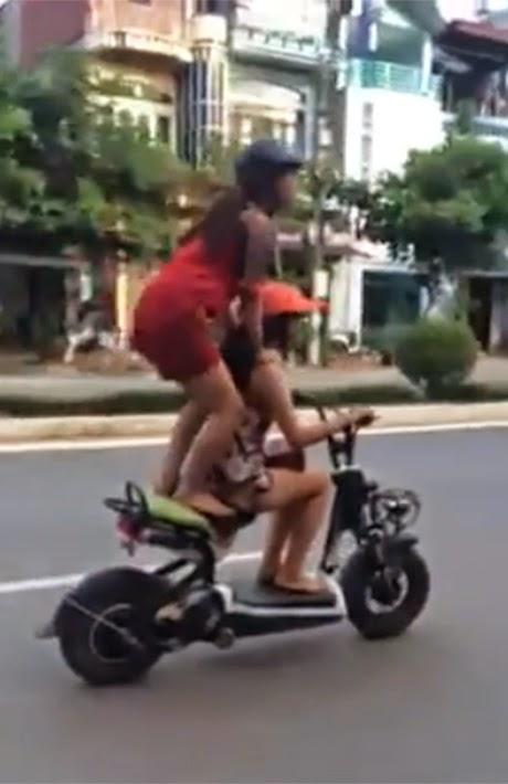 Trong clip, hai cô gái vừa đi vừa cười đùa, một cô đứng lên yên xe, dang hai tay... đi được một đoạn thì chiếc xe đổ