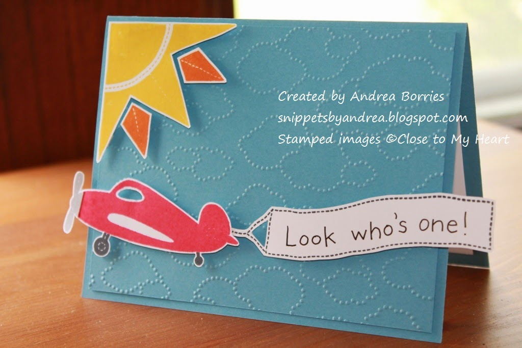 "Blue card with clouds embossed on the background and a stamped and cut-out sun and airplane pulling a banner that says ""Look who's one!"""