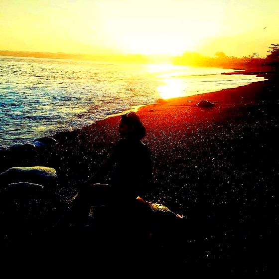 A girl sitting on the beach back to the sunset