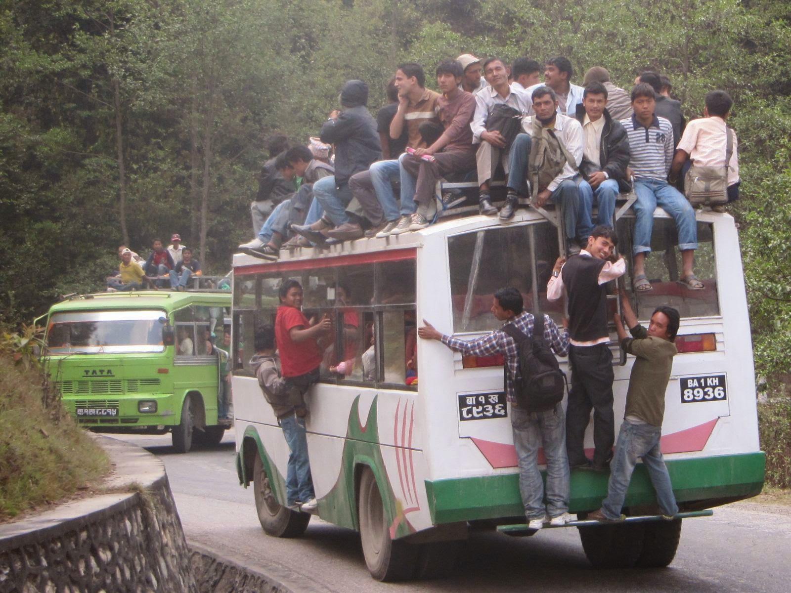 يركب الناس فوق أسطح الحافلات