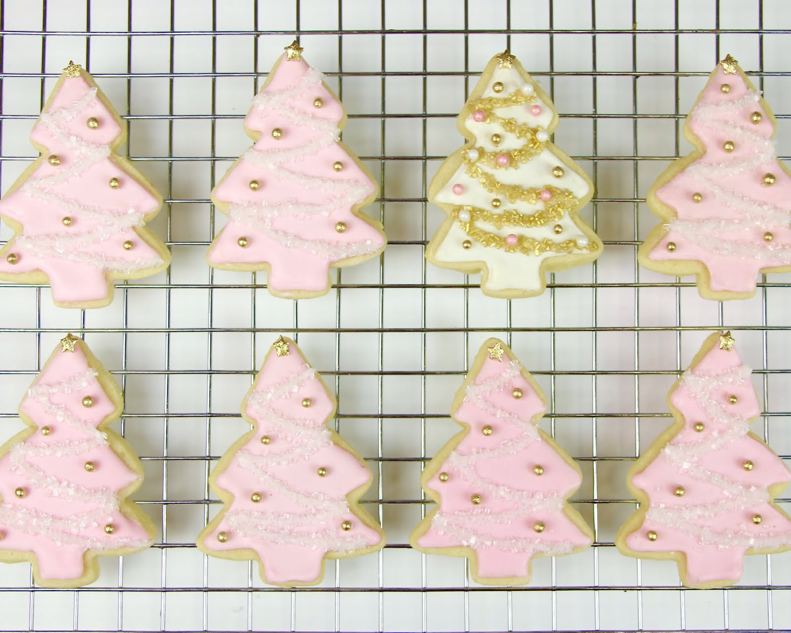 the most gorgeous cookies of the holiday season these super whimsical christmas tree cookies are covered in sweet pink icing glittering sugar sprinkles