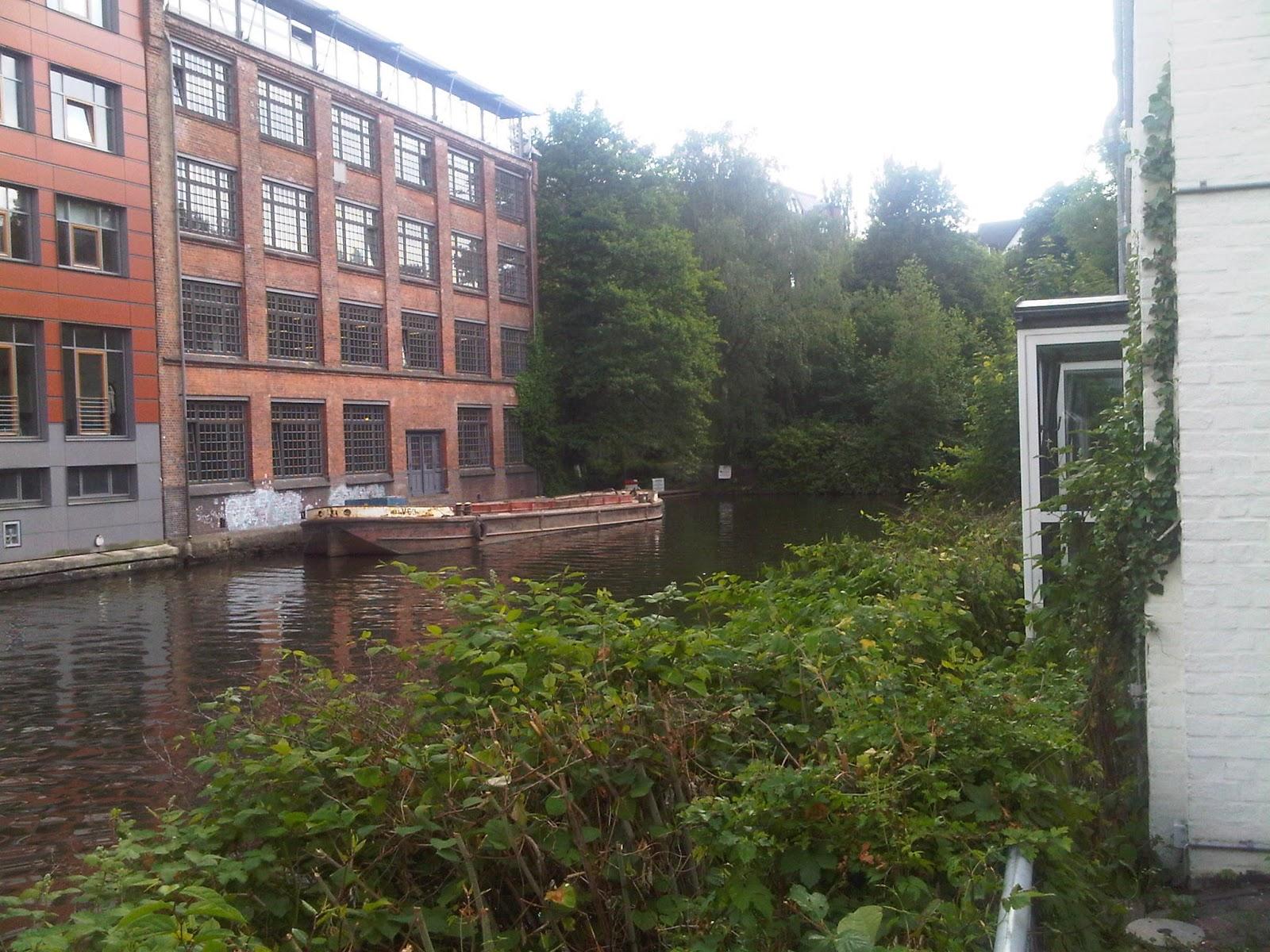 Goldbeckkanal mit Schute und altem Gebäude. Wasser, Büsche. Rotklinker-Fassade.