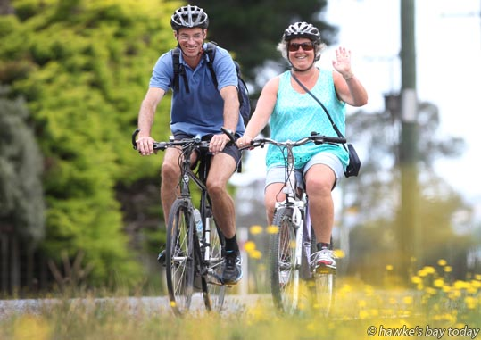 L-R: Dave Hanley, Linda Hanley, Wellington, cycling, riding their bikes, bicycles along Maraekakaho Rd, Hastings, in warm cloudy overcast weather, on a wine trail, visiting wineries. photograph