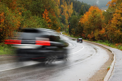 cars driving on damp fall road