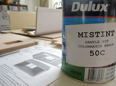One litre tin of mistint paint, marked 50c, on a table in front of pieces of a dolls' house miniature kit.