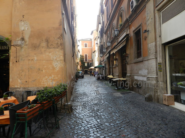Cobblestone street or alleyway with tables for cafe guests