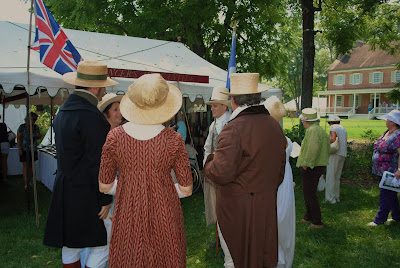 many people dressed in costumes from the 1800s with staw hats on the ladys and men shoping at the jane austen festival