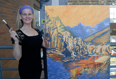 This photo shows 9/11 artist Kathleen Tonnesen. who received a diploma in early childhood education and is getting a certificate in performing and fine arts, posing with an oil painting at Douglas College's New Westminster Campus.