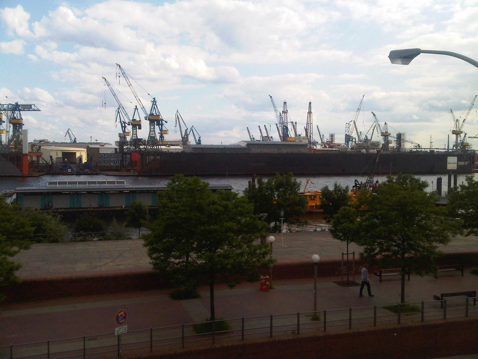 Blick auf die Containerverladung im Hamburger Hafen. Hafenstraße, Brücke, Wolken, blauer Himmel. Kräne.