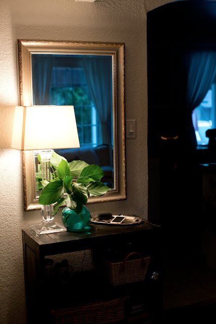 Entryway vignette using a lamp, vase, and mirror.