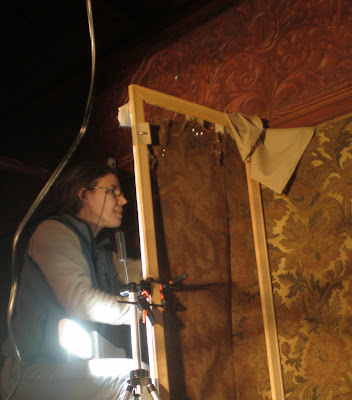 Art conservator at work, cleaning, restoration and repair of historic textile wall coverings, art conservation