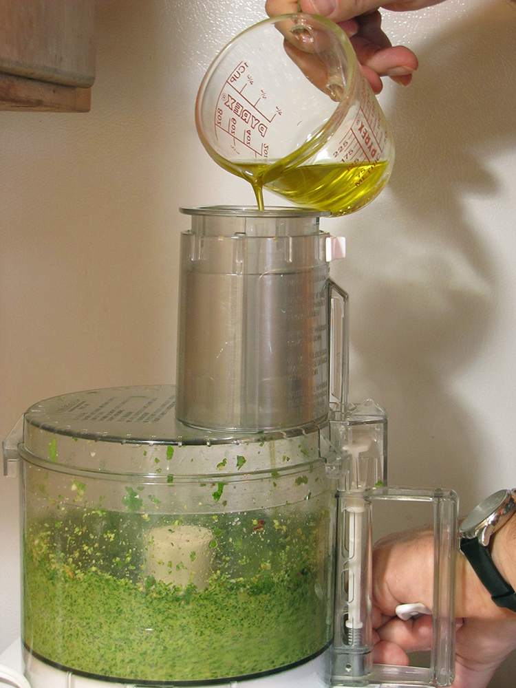 Pouring Olive Oil into Food Processor while Blending Pesto