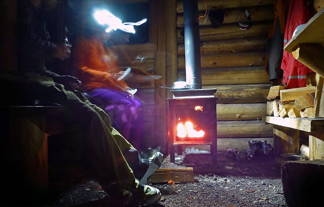 making jiffy pop popcorn on a wood stove in a ski shelter
