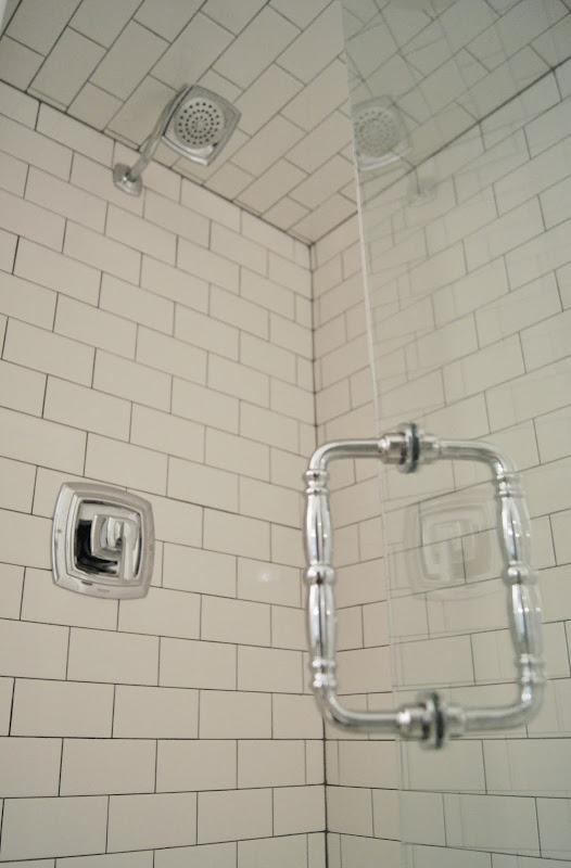 The shower walls are American Olean white subway tile with dark gray  title=