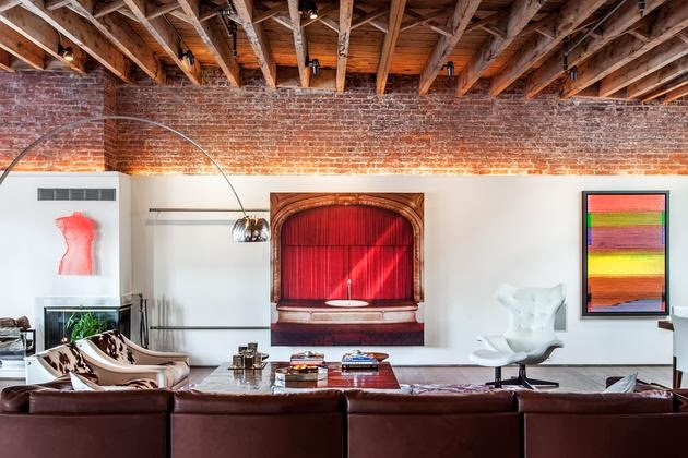 loft con techo de vigas de madera y pared de ladrillo visto