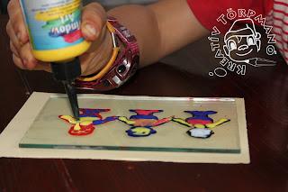 Szöveg: Ezek itt Törpmanó ikrecskék... Kép: Az előbb általam megrajzolt ikrek átkerültek a megrendelőhöz, aki épp sárga festékkel színezi az utolsó. A többi Törpmanó kék, piros, narancssárga, fehér színekben pompáznak.