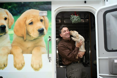 Mick smiles as a gets a kiss from a young puppy (yellow Lab) while standing under some mistletoe on the steps of the Puppy Truck.