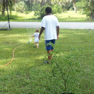 Big brother helping baby play in the water sprinkler and having fun with his brother.