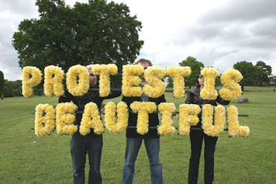 photo of three people holding letters made of yellow flowers that spell protest is beautiful