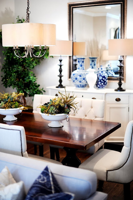 a dining room with life plants centerpiece and nearby is a buffet holding blue vases