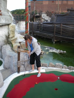 Emily plays hole 1 of the Warrior Trail course as a Crocodile (or Alligator) looks on