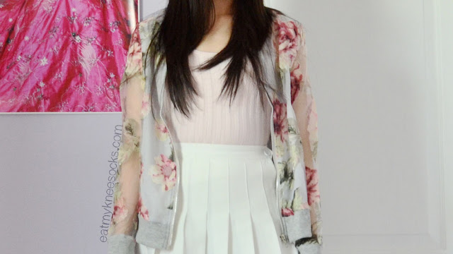 Close-up of the ulzzang-style outfit featuring the Dresslink floral bomber jacket, a white pleated American Apparel tennis skirt, and a cropped pastel pink top.