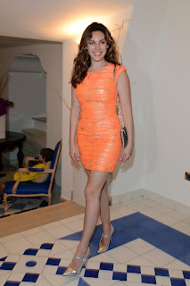 Kelly Brook strikes a pose for cameras in an orange dress