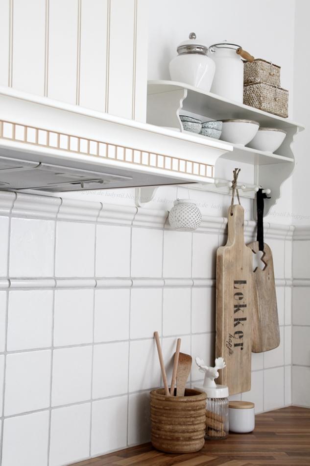 Blick an der Dunstesse vorbei zum weißen Wnadregal mit weißen und hölzernen Küchenaccessoires
