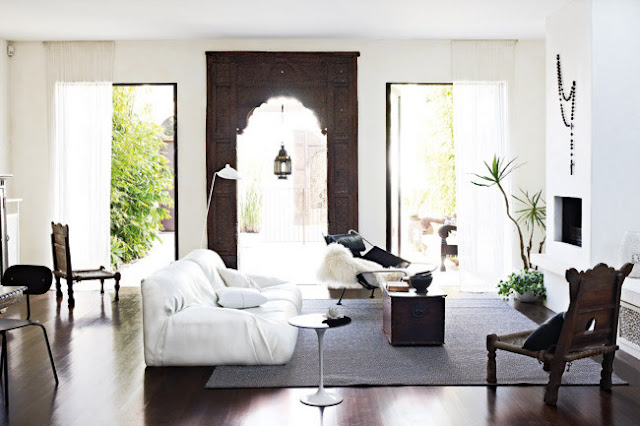 living room with carved wood portal doorway, white washed walls, a white sofa, dark wood floors and Moroccan inspired wooden chairs