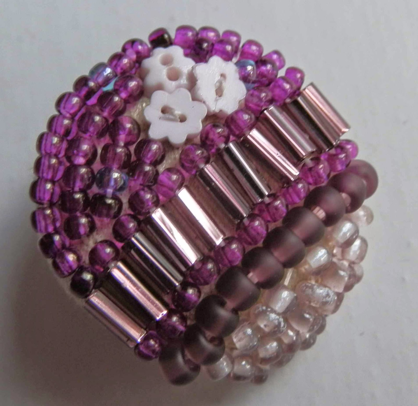 Beaded button featuring purple and pink beads