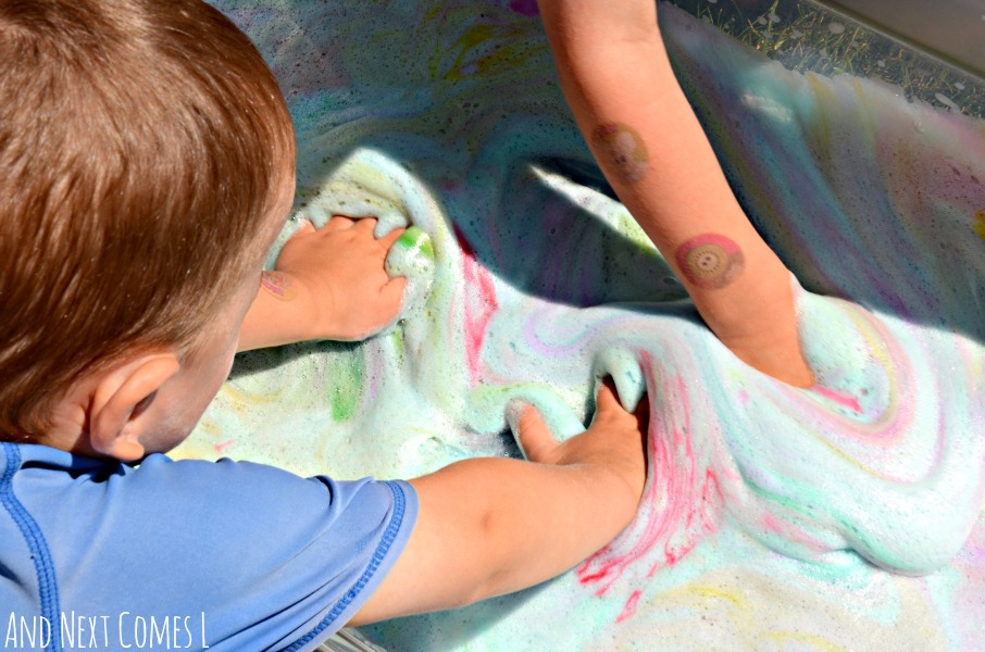 Sensory play for toddlers and preschoolers with colorful tie dye soap foam from And Next Comes L