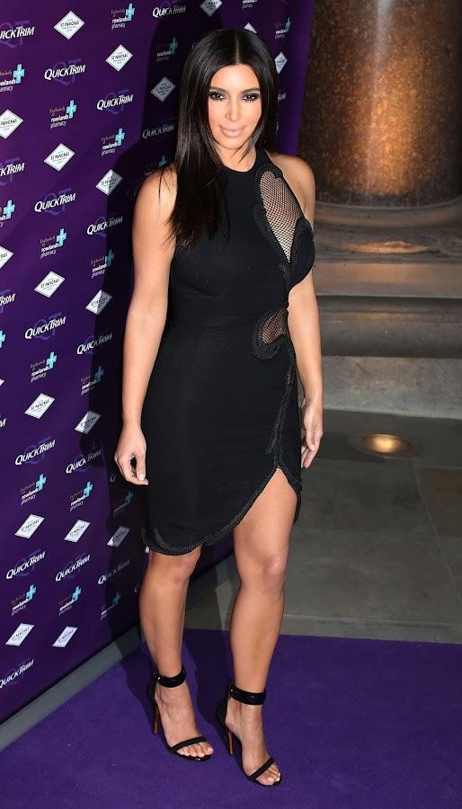 Kim Kardashian in a tight black dress with cutaway mesh panels
