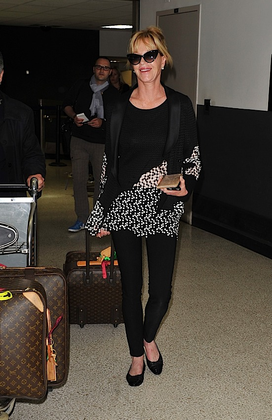 y luego por supuesto est la maleta de louis vuitton pegase melanie griffith parece tener una en la mano y varios ms en su carrito de equipaje