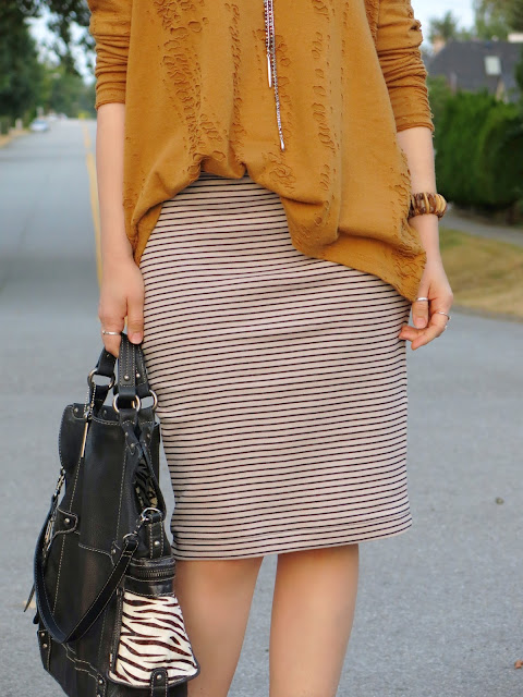 styling a striped pencil skirt with a distressed, long-sleeved tee and a Fossil bag