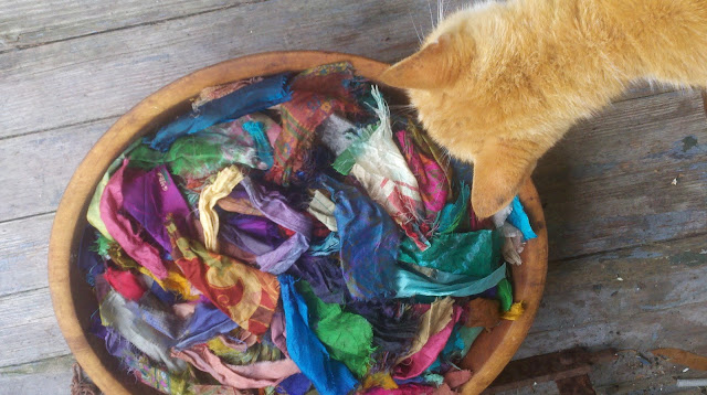 bowl full of salvaged sari silk scraps with my cat investigating