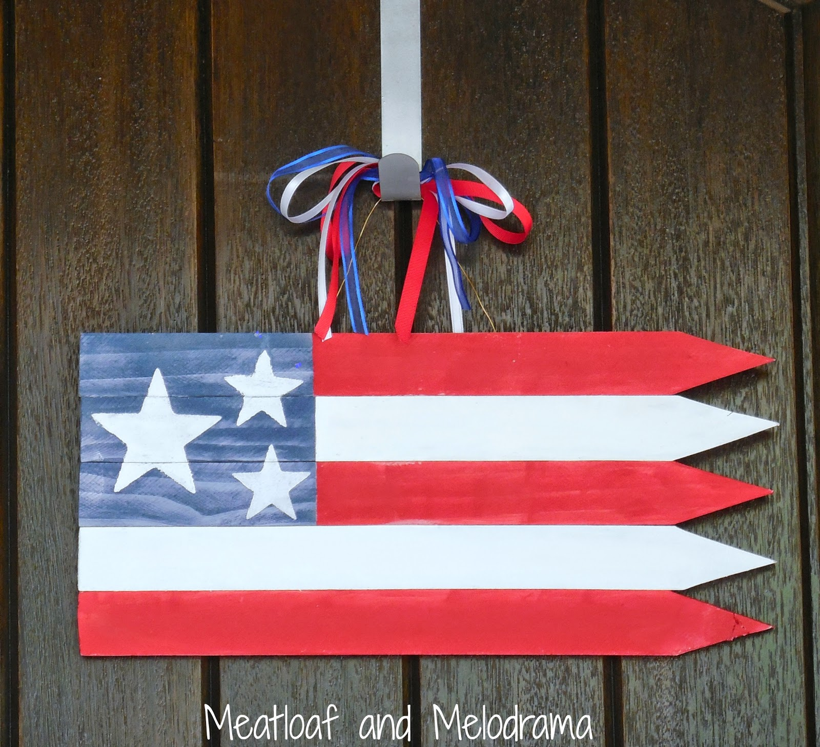 wooden American flag with red, white and blue ribbons