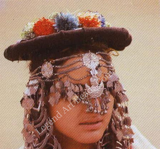 Under her hat decorated with dried flowers, the bride wears the tanaule across her forehead, silver leaves falling over her eyes.