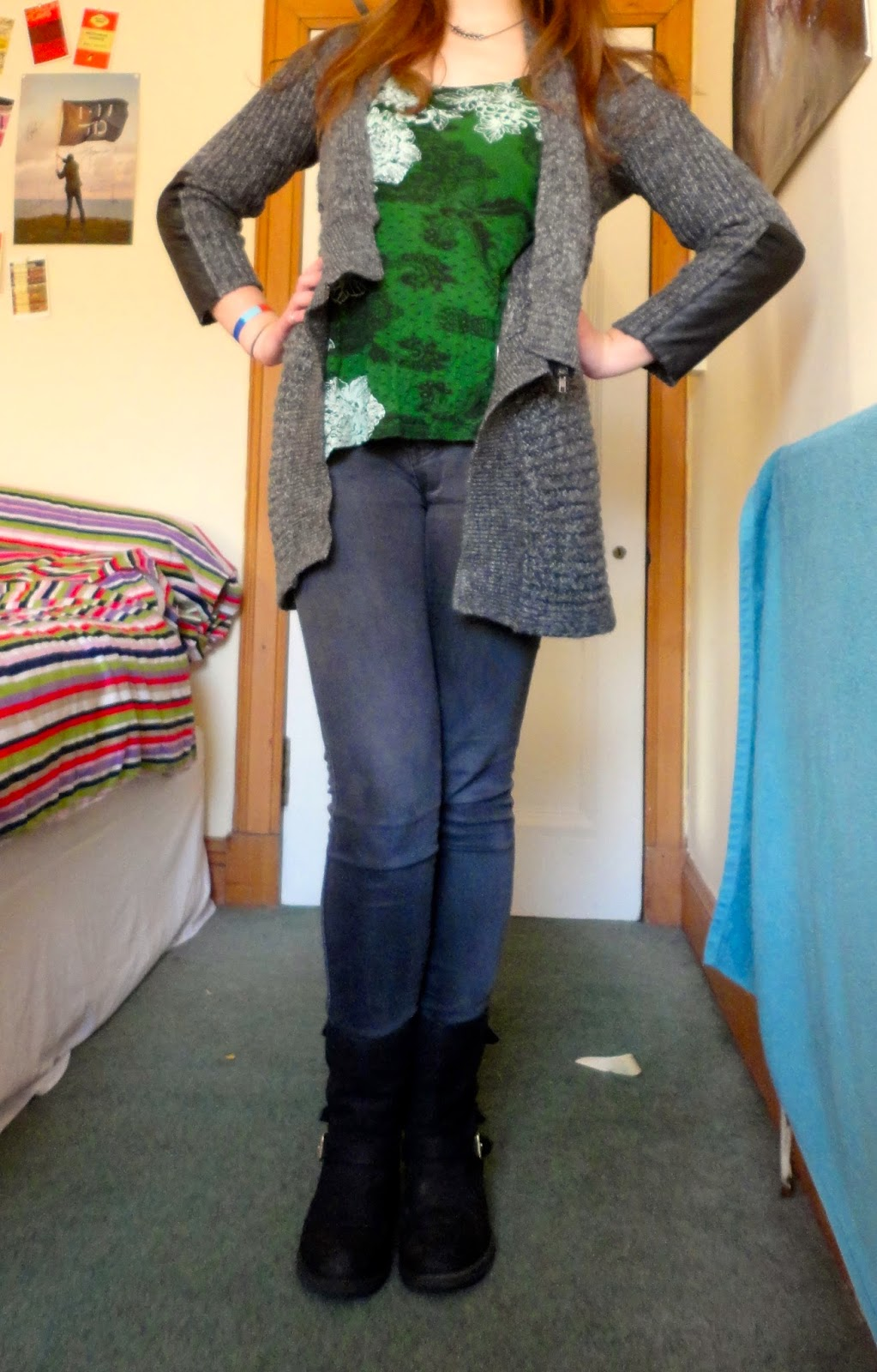 Winter outfit of grey cardigan, green top, jeans and boots