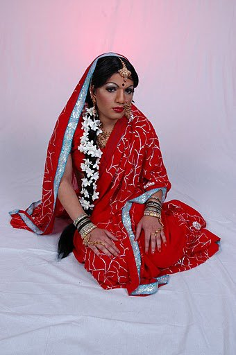 girl in red saree with long wavy hair and jasmine on her hair is a man