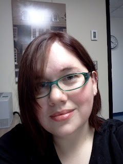 Self-portrait on my phone. Picture shows me, wtih dark red hair, green glasses, black shirt. Background is a white wall with framed picture of a campus building.