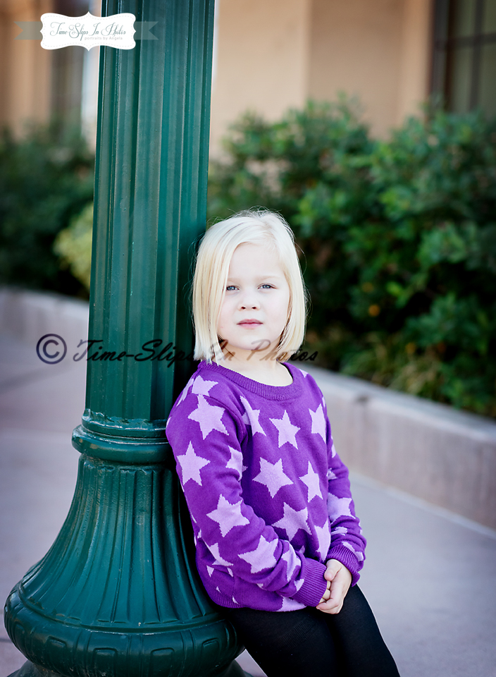 blond_toddler_girl_star_sweater_leaning_against_lamp_post