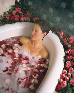 женщина принимает ванну с лепестками роз