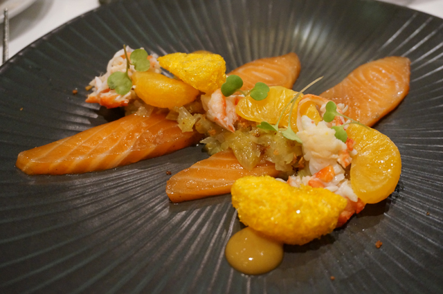 the devonshire: lightly cured king salmon, alaskan crab, fresh & freeze dried mandarin, golden raisin, roquette