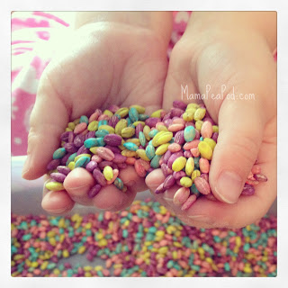 Child's hands holding rainbow-coloured barley grains for sensory play