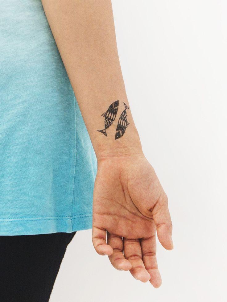 chica vestida de azul turquesa , con tatuaje pequeño de dos peces en el antebrazo
